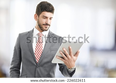 Portrait of young broker holding digital tablet in his hands. - stock photo