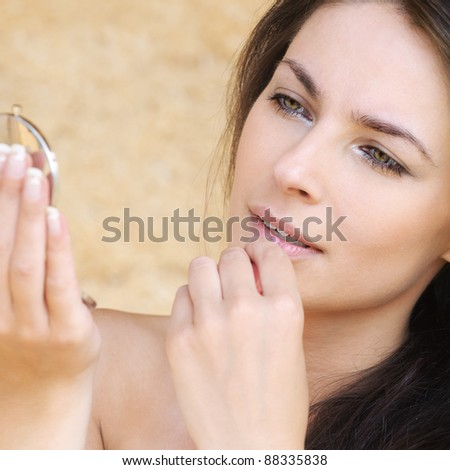 Portrait of young brunette beautiful woman looking at herself in mirror against beige background. - stock photo