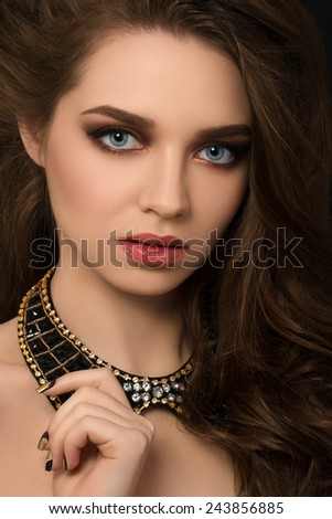 Portrait of young brunette beautiful woman with golden manicure touching her necklace - stock photo