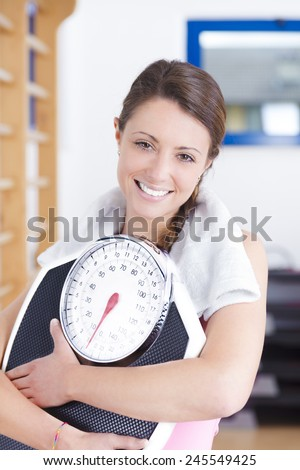 portrait of young brunette fitness woman with scale - stock photo
