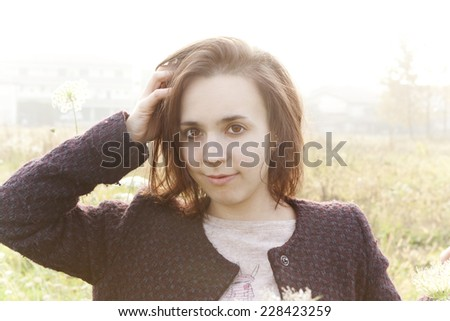 portrait of young brunette girl in the countryside with natural sunny backlight  - stock photo