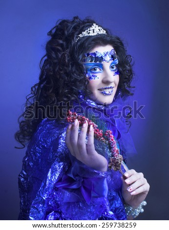 Portrait of young brunette in creative carnival image. - stock photo
