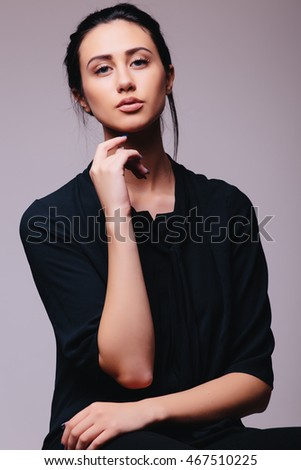 Portrait of Young brunette lady in black  posing on grey background