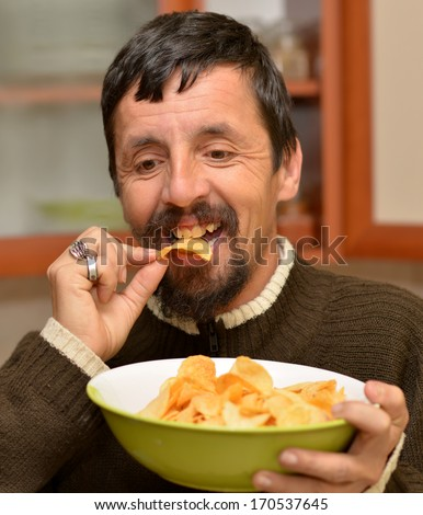 Portrait of young brunette man eating chips - stock photo