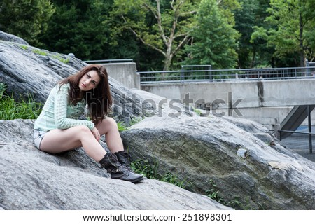Portrait of young brunette sitting on the bouders in the park - stock photo