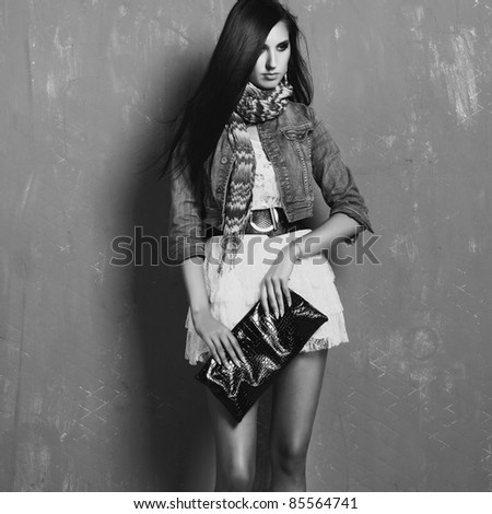 portrait of young brunette woman in jeans jacket posing - stock photo