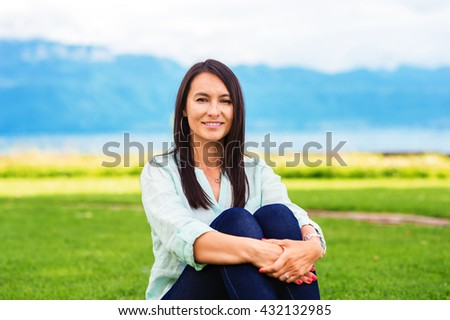 Portrait of young brunette woman resting outdoors - stock photo