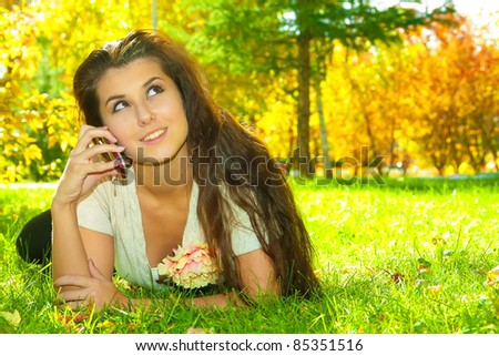 Portrait of young brunette woman speaking on mobile phone at green park - stock photo
