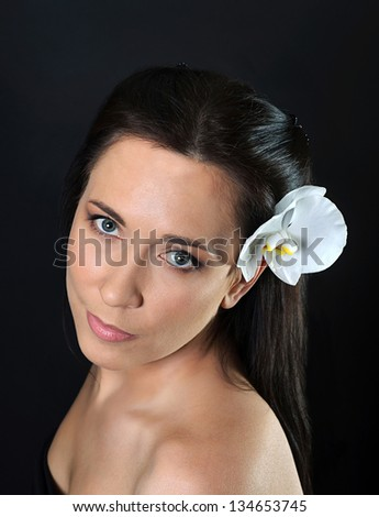 portrait of young brunette woman with white orchid in hair looking at camers - stock photo