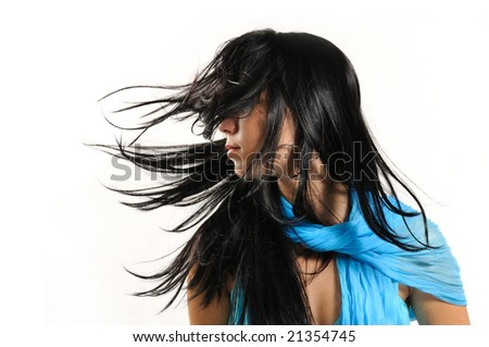 Portrait of young brunette woman with wind blowing hair