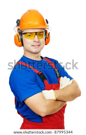 Portrait of young builder in protective safety equipment goggles hard hat earmuffs isolated - stock photo