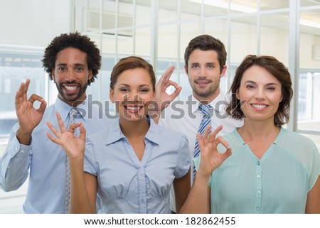 Portrait of young business colleagues gesturing okay sign in the office - stock photo