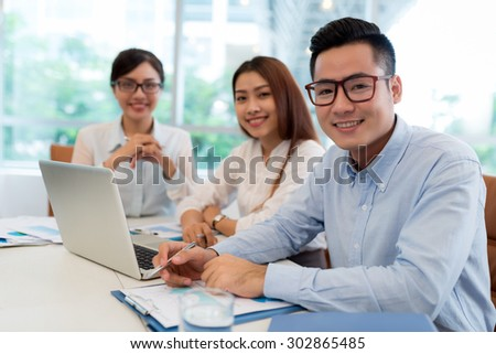 Portrait of young business colleagues working together with laptop in the office