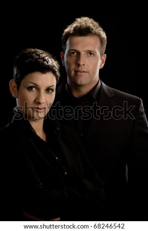 Portrait of young business couple in black, isolated on black background.?