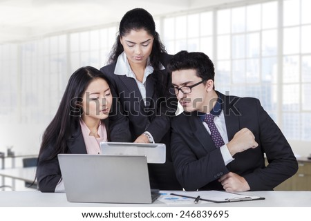 Portrait of young business leader showing business plan on tablet at her team in the business meeting
