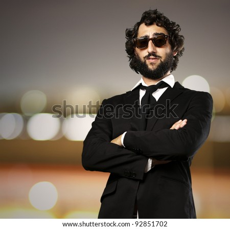 portrait of young business man against a city by night