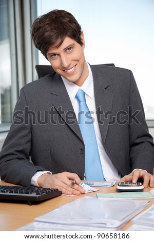 Portrait of young business man calculating budget using calculator at office - stock photo