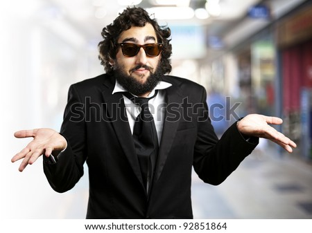 portrait of young business man confused against a crowded place - stock photo