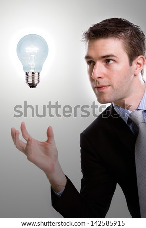 Portrait of young business man holding a light bulb - stock photo