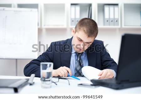 Portrait of young business man in the office doing some paperwork