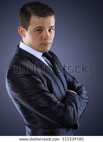 Portrait of young business man isolated over dark background - stock photo