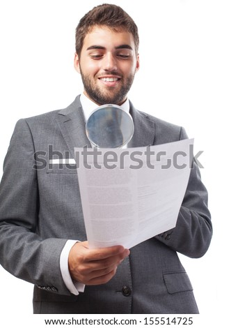 portrait of young business man looking a contract through a magnifying glass on white - stock photo