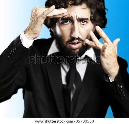 portrait of young business man looking in the mirror against blue background