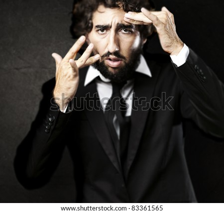 portrait of young business man looking to mirror against a grunge background - stock photo