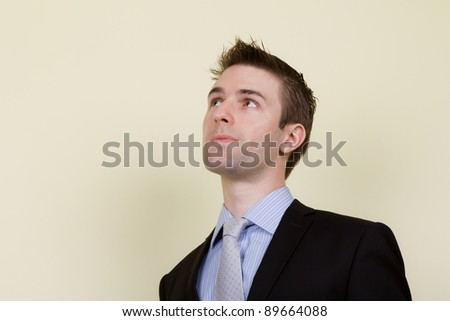 Portrait of  young business man looking up - stock photo