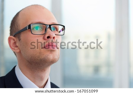 Portrait of young business man looking up in office with view to window - stock photo