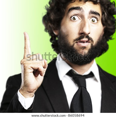 portrait of young business man pointing up against a green background - stock photo