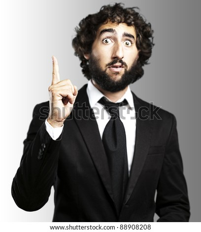 portrait of young business man pointing up against a grey background - stock photo