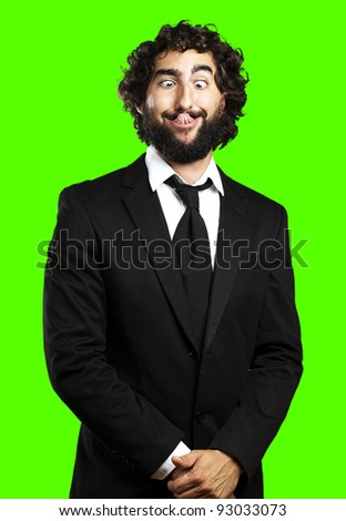 portrait of young business man showing the tongue against a removable chroma key background