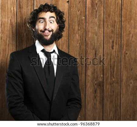 portrait of young business man showing tongue against a wooden wall - stock photo