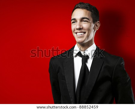 portrait of young business man smiling against a red background - stock photo