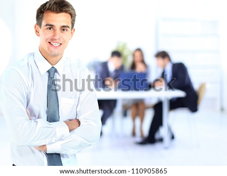 Portrait of young business man smiling with colleagues in background - stock photo