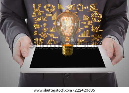 Portrait of young business man using a touch screen device with bulb and business graph - stock photo