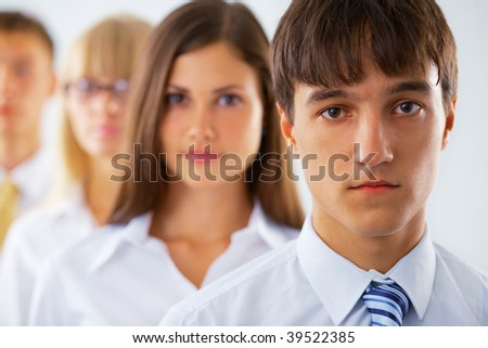 Portrait of young  business man with his colleagues standing in a row - stock photo