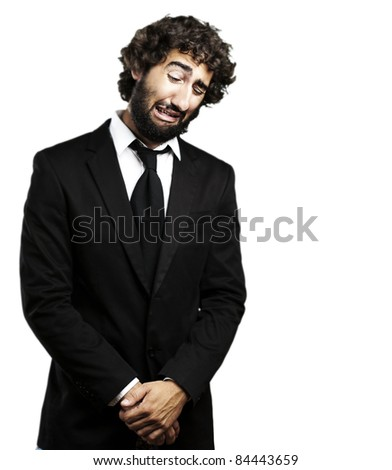 portrait of young business man with suit crying against a white background - stock photo
