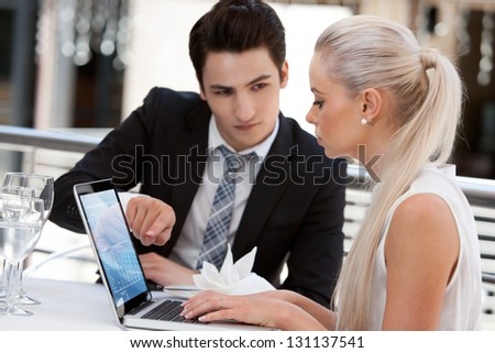 Portrait of young business partners working on laptop during lunch. - stock photo