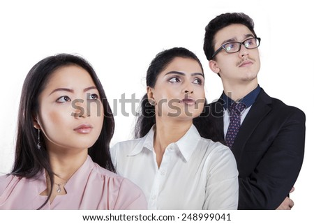 Portrait of young business people standing in a row while looking at copy space - stock photo
