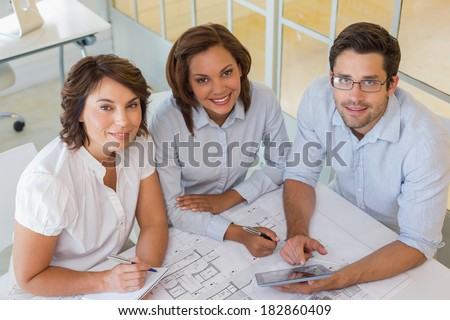 Portrait of young business people working on blueprints and digital tablet at the office