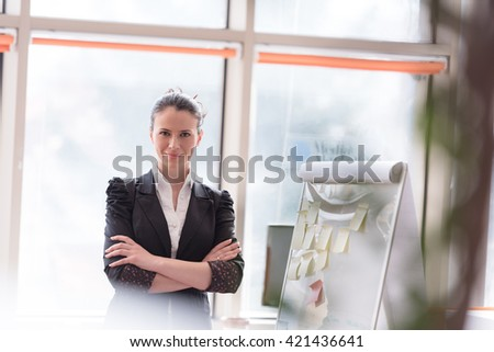 portrait of young business woman at modern office with flip board  and big window in background - stock photo