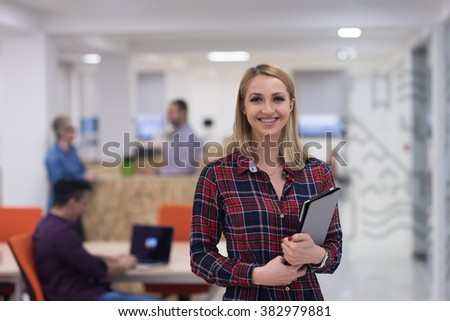 portrait of young business woman at modern startup office interior, team in meeting in background - stock photo
