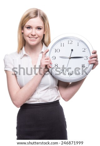 Portrait of young business woman is holding in hands clock, isolated on white background, discipline and punctual concept.