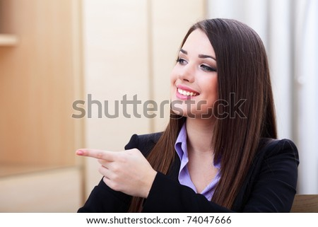 Portrait of young business woman pointing aside at copyspace - stock photo