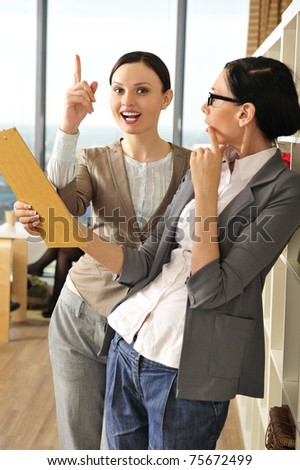 Portrait of young business woman pointing up and her colleague holding documents and reports . At an office environment - stock photo