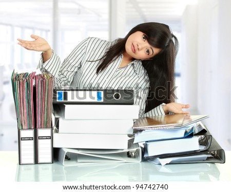 Portrait of young business woman showing document on the table - stock photo