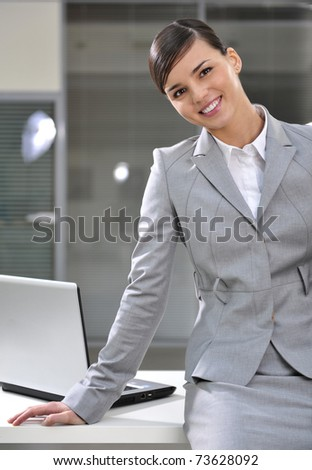 Portrait of young business woman sitting at corner of her desk - Copyspace - stock photo