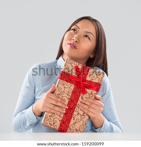 Portrait of young business woman sitting at her desk with a gift box - stock photo